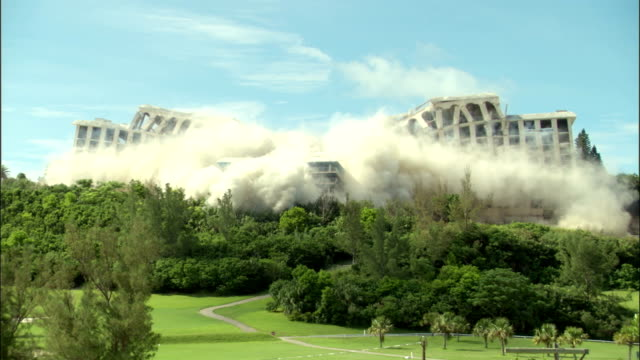 vidéos et rushes de ws hotel in resort setting is demolished in controlled implosion using explosives / st. george's , bermuda - imploding