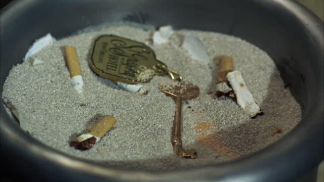 1967 CU Hotel key falling into sanded ashtray with cigarette butts