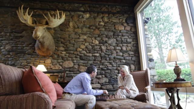 vídeos de stock e filmes b-roll de hotel lobby man woman husband wife couple chess board chess pieces chess game holiday vacation resort getaway lodge  - cabana de madeira