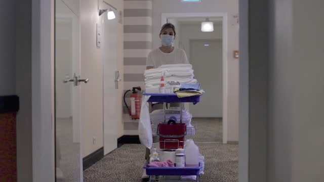 hotel maid pushing cart through corridor - one mid adult woman only stock videos & royalty-free footage