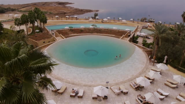 ws - hotel pool with dead sea in the background. jordan, middle east - tourist resort stock videos & royalty-free footage
