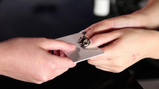 hotel receptionist hand over the hotel key card to hotel guest - offrire un servizio video stock e b–roll