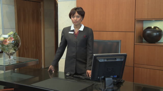 ms pan hotel receptionist standing by desk / cape town, cape town, south africa - 真剣点の映像素材/bロール