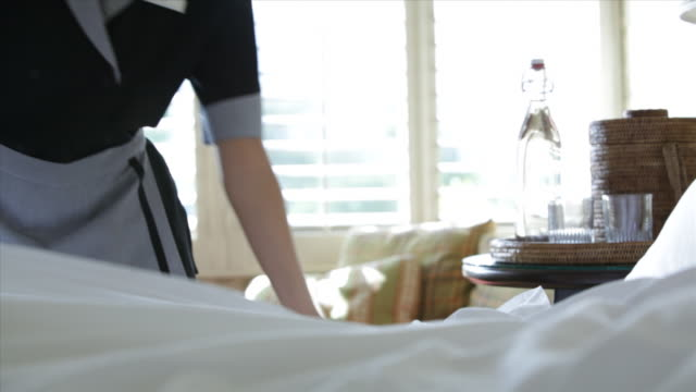 hotel resort getaway lodge bedroom bed sheets woman maid housekeeper making bed - ホテル点の映像素材/bロール