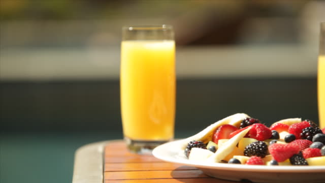 hotel resort lodge pool deck deck chairs breakfast fruit bowl orange juice holiday vacation getaway - orange juice stock videos & royalty-free footage