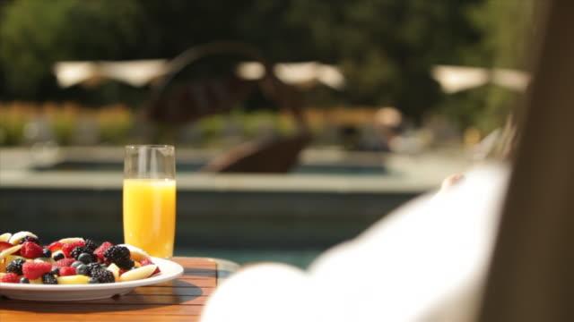 vídeos y material grabado en eventos de stock de hotel resort lodge pool deck deck chairs guests bathrobes breakfast fruit bowl orange juice holiday vacation getaway - zumo de naranja