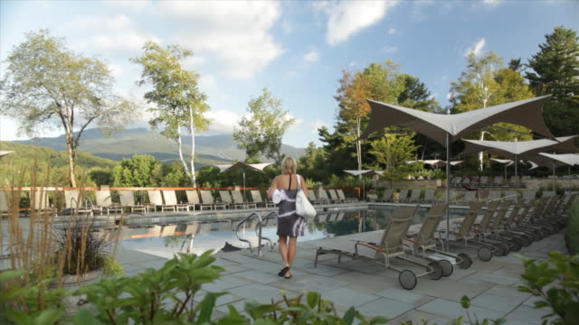 hotel resort lodge pool pool deck deck chairs flowers plants woman guest swimmer bathing suit