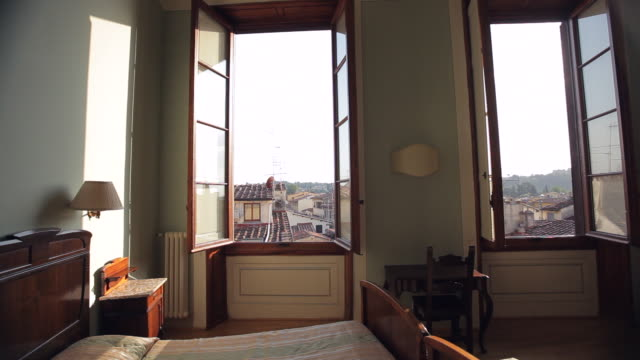 ws ds hotel room interior with sun shining through window / florence, italy - abwesenheit stock-videos und b-roll-filmmaterial