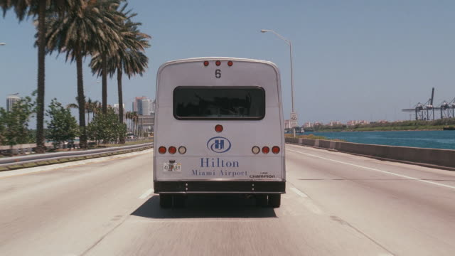 stockvideo's en b-roll-footage met a hotel shuttle bus approaches the miami skyline on the macarthur causeway bridge from the pov of a trailing vehicle. - macarthur causeway bridge