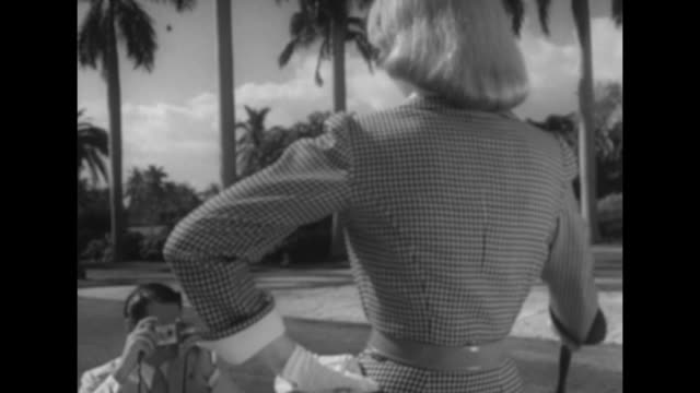 vídeos y material grabado en eventos de stock de hotel through gates, fashion models mark and joan walk out / from behind mark holding camera pointed at joan wearing check wool dress, holding... - camisola