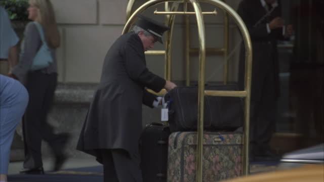 vídeos y material grabado en eventos de stock de ms hotel valet arranging luggage onto rack for guests / new york city, new york, usa - hospitalidad
