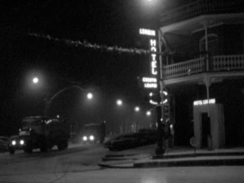stockvideo's en b-roll-footage met hotel w/ lit neon sign on corner of street two trucks driving along snow covered street frame one pedestrian by entrance of hotel wi - street name sign