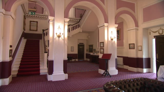 Hotel with grand staircase and red carpet, pan to staff working, Norfolk, England
