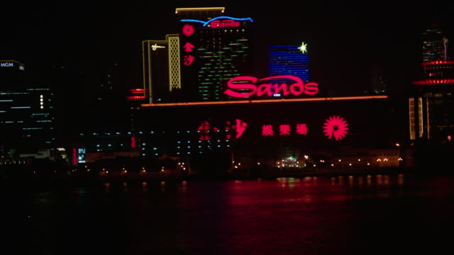 hotels & casino high & mid-rise buildings w/ colorful lights & large sands sign on waterfront, bridge railing fg. - macao stock-videos und b-roll-filmmaterial