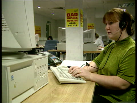 vidéos et rushes de hotline to name and shame bad bosses itn tyne tees workers sitting talking on phones in office with posters up 'bad bosses hotline amp phone number' - embarras