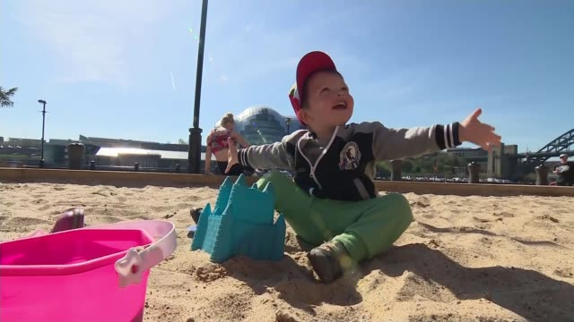hottest april day since 1949; newcastle-upon-tyne: ext young boy plays in sandpit in city centre woman sits sunbathing in deckchair - deck chair stock videos & royalty-free footage