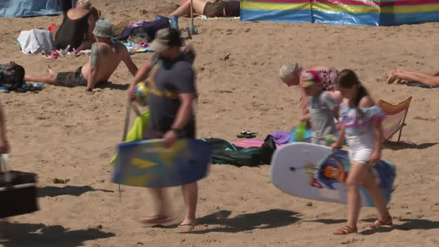 hottest day of the year so far; england: devon: exmouth: ext various of crowds sunbathing and sitting on busy beach long shots of people swimming and... - beach stock videos & royalty-free footage