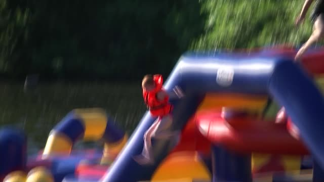 thorpe aqua park at chertsey england surrey chertsey reporter to camera children on inflatable obstacle course on water ben hounslow live interview... - obstacle course stock videos & royalty-free footage