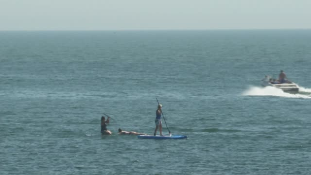 hottest ever bank holiday weekend recorded england devon exmouth ext holidaymakers on beach speedboat and paddle boards along sea speedboat along sea... - buried stock videos & royalty-free footage