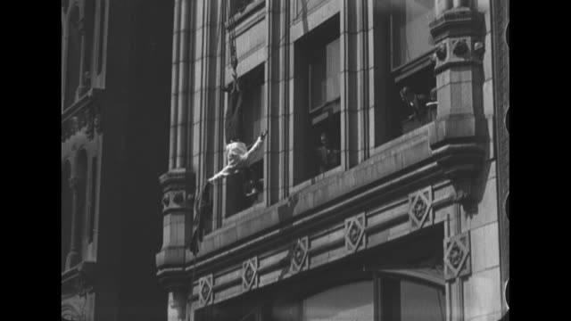 Houdini is hoisted into the air upside down and lifted high above the crowd as he wrestles himself loose from a straightjacket