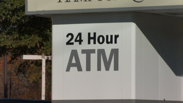 hour atm painted lettering sign on outdoor drive-up automated bank teller machine. shaky. - banking sign stock videos & royalty-free footage