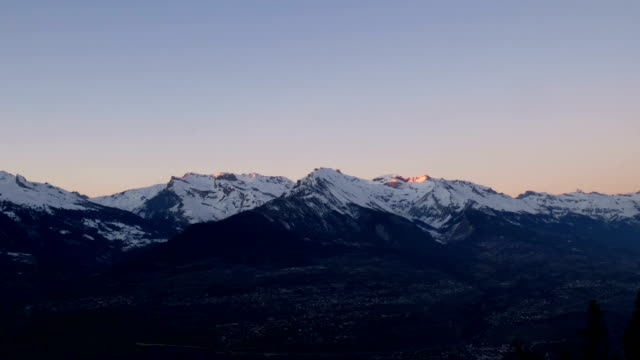 a 24 hour  day to night to day timelapse of clouds, mountains and an alpine town in the valley below. - schweizer alpen stock-videos und b-roll-filmmaterial