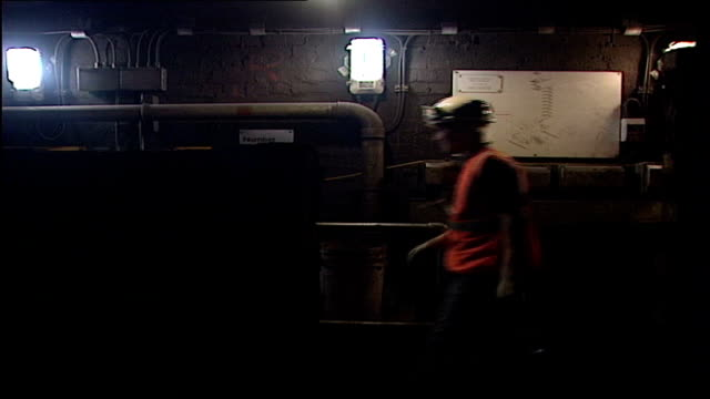 Underground at night ITN ENGLAND London Underground rail maintenance workers along in hard hats to hidden underground entrance INT GVs Workers along...