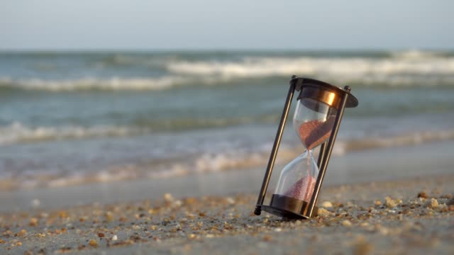 hourglass on the beach sand beach. saving time concept - hourglass stock videos & royalty-free footage