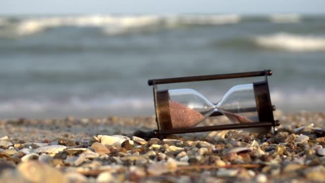 Timglas sand stranden. Spara tid-konceptet