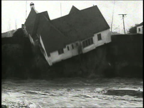 B/W 1936 house falling off of cliff into floodwaters below
