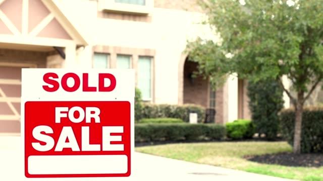 Haus zu verkaufen mit Immobilienschild im Hof.