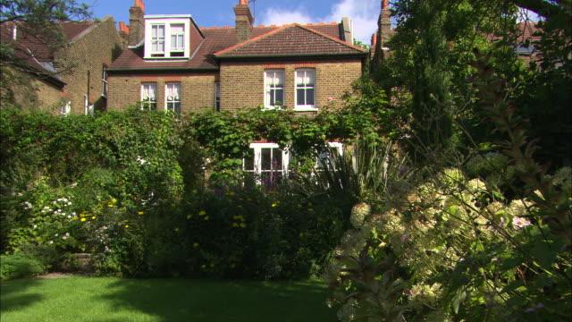 vídeos y material grabado en eventos de stock de ms of house, garden, flowers in fg (lock-off) - jardin