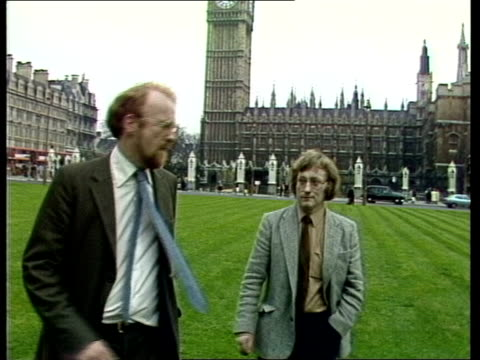 house of commons row; england: london: parliament square: david rose and ron brown walk along parliament square r-l both on lawn zoom in ron... - house of commons stock videos & royalty-free footage