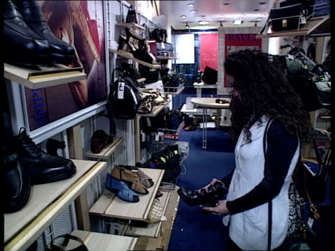 house of fraser sell off itn lib ms woman looking at platform shoes in shop tcms woman trying shoe on cs platform show being tried on ms woman trying... - platform shoe stock videos and b-roll footage