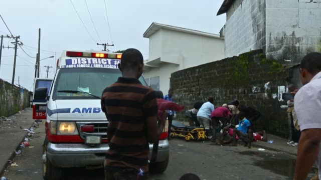 vídeos de stock, filmes e b-roll de house of representatives member, saah joseph, attends to wounded in this morning's clash between police and members of west point, the largest slum... - febre hemorrágica