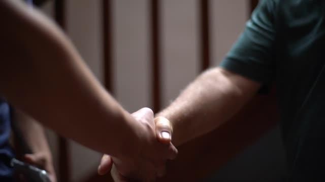 vidéos et rushes de propriété de la maison et son invité sur la poignée de main - se saluer