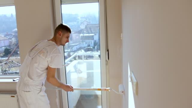 stockvideo's en b-roll-footage met de schilder die van het huishuis in witte collor schildert - verfkwast