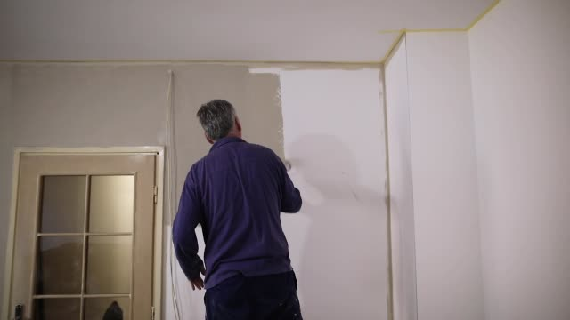 house painter painting residential home interior in gray color - repatriation stock videos & royalty-free footage