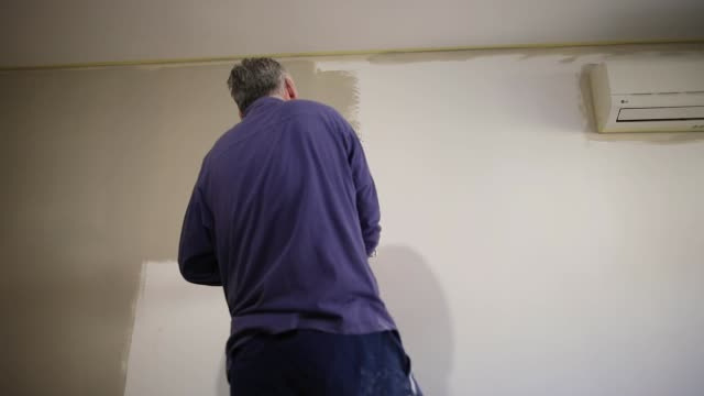 house painter painting residential home interior in gray color with paint roller - ladder stock videos and b-roll footage