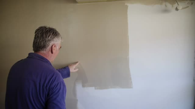 house painter painting residential home interior in gray color with paint roller - paint roller stock videos & royalty-free footage