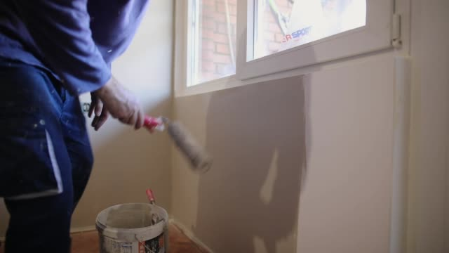 house painter painting residential home interior in gray color with paint roller - repatriation stock videos & royalty-free footage