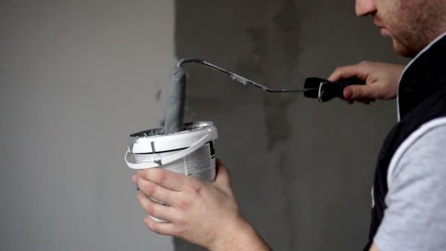 haus malerei und bau arbeiter mit farbroller - gebäudefront stock-videos und b-roll-filmmaterial