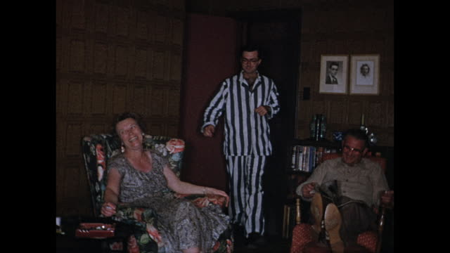 1955 MONTAGE House party, man wearing striped pajamas coming into room and going to bed / Port Credit, Ontario, Canada