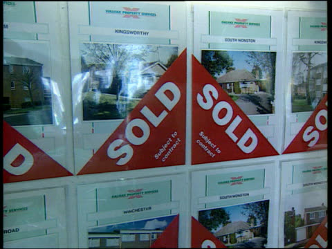 stockvideo's en b-roll-footage met sold sign put over property details in estate agents window for sale sign outside house pull out gv sale boards outside houses - for sale korte frase