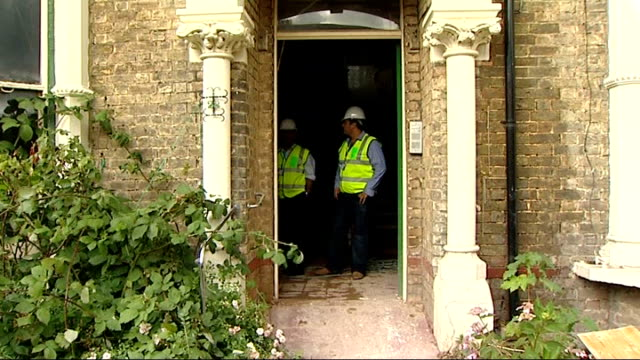 house renovation / housing development construction site england london ext exteriors of semidetached house under renovation boarded up front yard... - hammer stock videos and b-roll footage