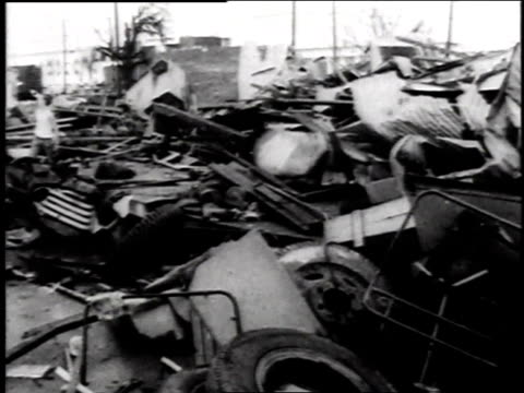house with front wall ripped off / rubble from destroyed build and vehicles / company's sign leaning against building / demolished office with rubble... - 1957 stock-videos und b-roll-filmmaterial