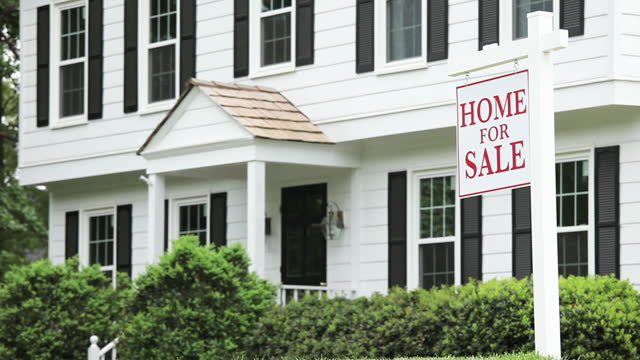 House with 'Home for Sale' sign in yard