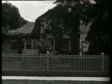 vídeos de stock, filmes e b-roll de b/w house with ivy and picket fence / 1920's / no sound - trepadeira