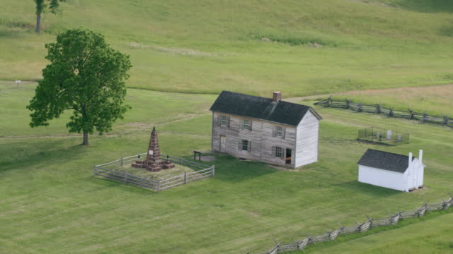WS AERIAL POV House with memorial structure and cannons on grassy landscape at Manassas National Battlefield Park / Manassas, Virginia, United States