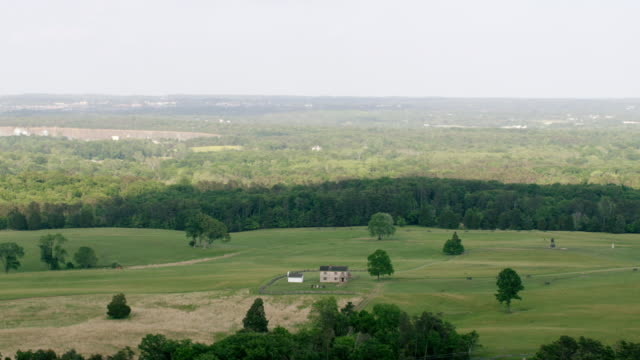 stockvideo's en b-roll-footage met ws aerial pov house with memorial structure on grassy landscape at manassas national battlefield park, forest in background / manassas, virginia, united states - memorial